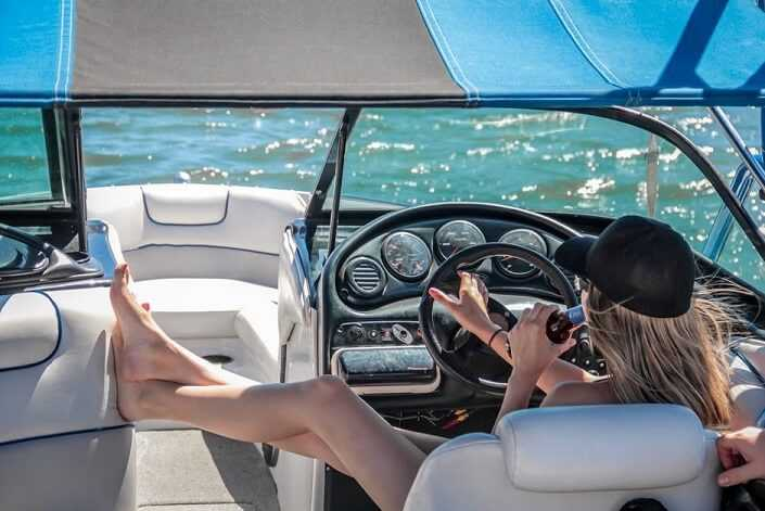 A young girl is driving a yacht while drinking.