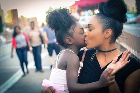 A single mom is kissing her baby